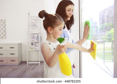Daughter and mother cleaning window together