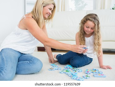 Daughter and mother doing a jigsaw puzzle on the floor