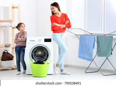 Daughter and mother doing laundry together at home