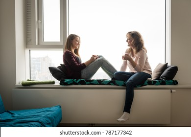 Daughter and mother having tea together, facing each other.