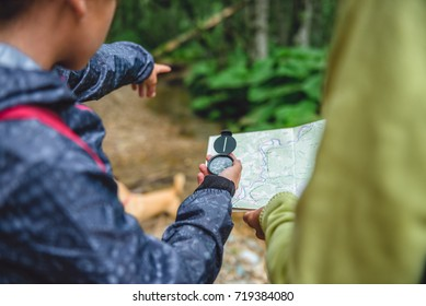 Daughter and mother hiking in forest using compass and map to navigate