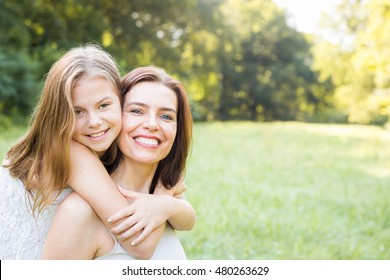 Daughter and mother hugging, happy and smiling over nature blurred background