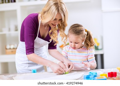 Daughter and mother make cookies in the kitchen