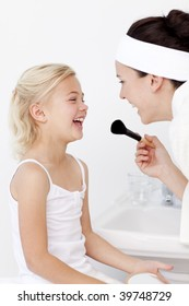 Daughter and mother playing with makeup in bathroom