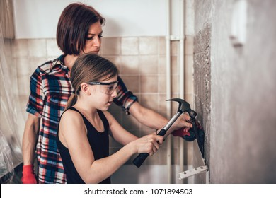 Daughter and mother removing old wall tails in the kitchen