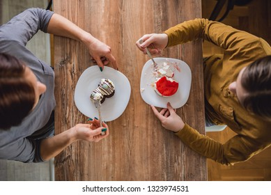 Daughter and mother sitting by the dining table at home and eating cheese and chocolate cake