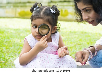 Daughter at outdoor green park with mother. Cute Indian girl peeking through magnifying glass with parent.