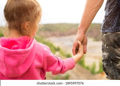 Daughter in a pink hoodie holding dad's hand, standing on top of a mountain with a beautiful panoramic view. Family camping, outdoor activities. Help and support, parenting, protection.