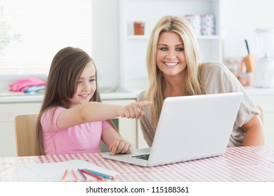 Daughter pointing at laptop with mother in the kitchen