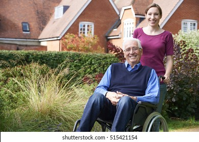 Daughter Pushing Senior Father In Wheelchair