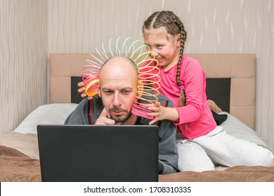 The daughter puts the slinky toy to the father's head. Family is quarantined at home. A little girl is making fun of dad.A child prevents a man from working on a laptop in his bedroom.