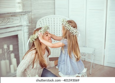 A daughter is putting a floral wreath on her mother. A mother is having jeans and white blouse on. The girl is having a light blues dress. The atmosphere of happiness is all around them.