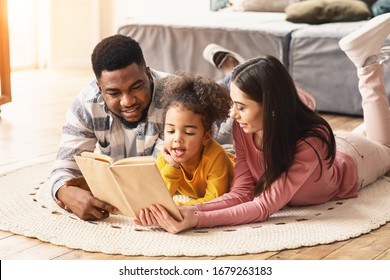 Daughter is reading book to her international parents on the floor at home