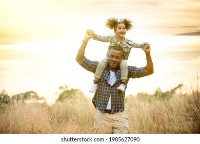 Daughter riding father's neck spending time outdoors happy family fun on the meadow at beautiful nature sunset.