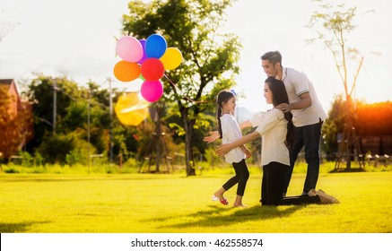 Daughter running to mother and father, She enjoyed the play balloons