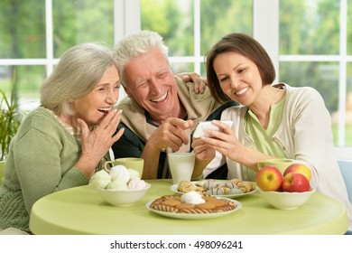 Daughter with senior parents drinking tea