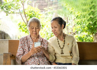 daughter showing her grandma how to use smartphone