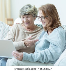 Daughter is showing old mother how to use a computer