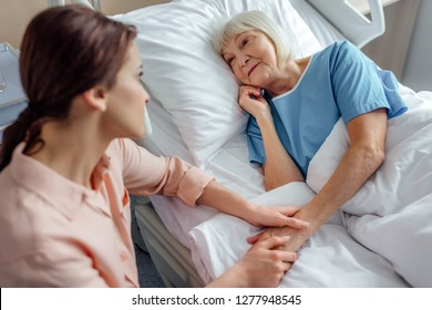 daughter sitting near senior mother in bed and holding hands in hospital