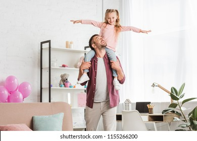 daughter sitting on fathers back and having fun