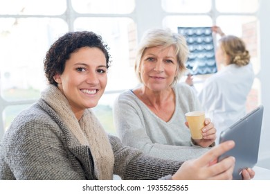 daughter and smiling senior woman holding a cup of coffee