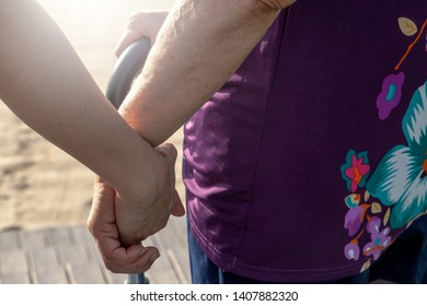 Daughter or son hold mother's hand to help her to walk carefully. This can be use to show how deep is the biggest love between them. This can be related with any article about family, elder, health.