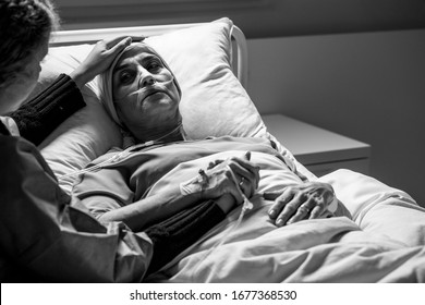 Daughter supporting sad, dying woman with tumor in a hospital, black and white photo