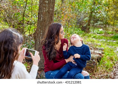 daughter taking mobile photo of mother and son brother in the park having fun