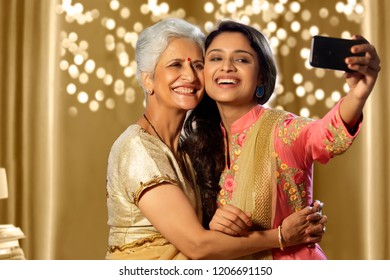Daughter taking a self portrait with mother using smart-phone in diwali festival
