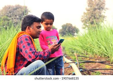 """daughter teaching his father (Farmer) Smartphone in farm """"Akole, Maharashtra  India - February 02 2020"""""""