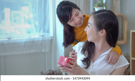 the daughter of a teenager is giving a gift to the mother on the special occasion of her mother