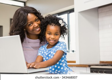 Daughter using laptop with mother in the kitchen