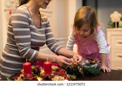 Daughter watching as her mother decorates christmas wreath