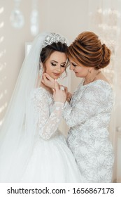 Daughter who became the bride gently embraces her mother. Mother of the bride blesses the bride for a happy family life.
