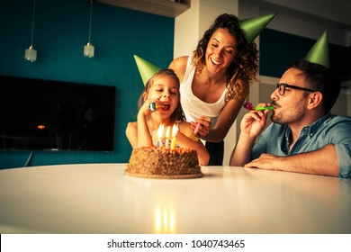 Daughter's birthday.Mom and dad surprise they daughter with birthday cake .