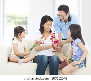 Daughters and father handing mother carnations