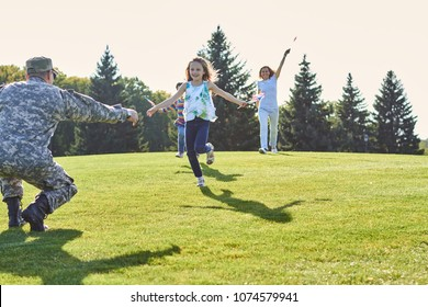 Daughters are running to their soldier father. Reunion of happy family on the meadow.