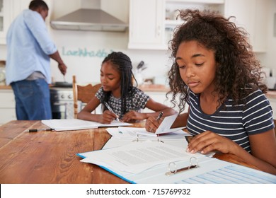 Daughters Sitting At Table Doing Homework As Father Cooks Meal