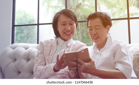 Daugther teaching mother to use smart phone for social media