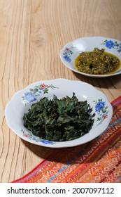 Daun singkong rebus (boilled cassava leaves) with green chili sauce.