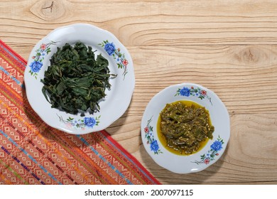 Daun singkong rebus (boilled cassava leaves) with green chili sauce, top view.