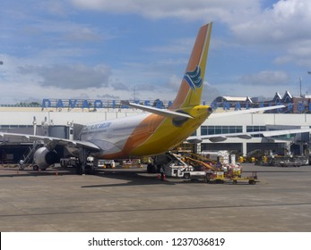 DAVAO CITY, PHILIPPINES—MARCH 2018: Rear view of a Cebu Pacific Airlines aircraft loading passengers and cargo at the Davao International Airport.