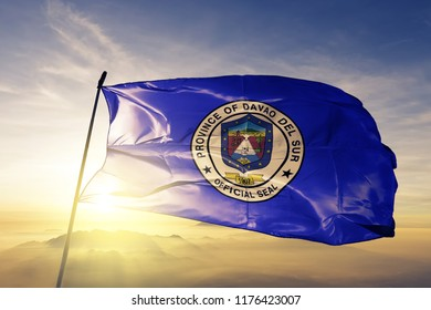 Davao del Sur province of Philippines flag textile cloth fabric waving on the top sunrise mist fog