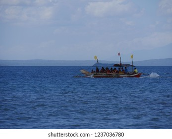 DAVAO NORTE, PHILIPPINES—MARCH 2018: A boat carries tourists on an island tour around Mabini, Davao del Norte coastline.