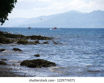 DAVAO NORTE, PHILIPPINES—MARCH 2018: Rocky beach view with boaters enjoying the waters along the coast of Davao del Norte, southern Philippines.