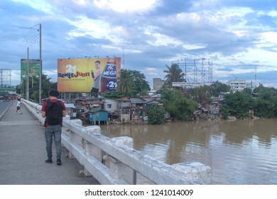 Davao, Philippines - November 25, 2018: Davao River with a village of informal settlers at the riverbanks. Part of Generoso Bridge is also visible and some pedestrians.
