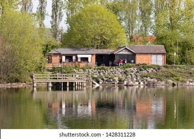 Daventry, Northamptonshire / UK - May 7th 2019: Reservoir Cafe, part of the country park's visitor centre, and bird viewing platform are reflected in the water. Two women sit with a mug of tea.