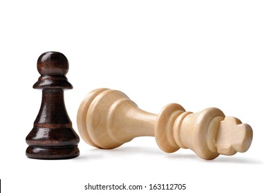 David and Goliath syndrome in chess with a small dark pawn standing triumphant over a fallen light wood king on a white background