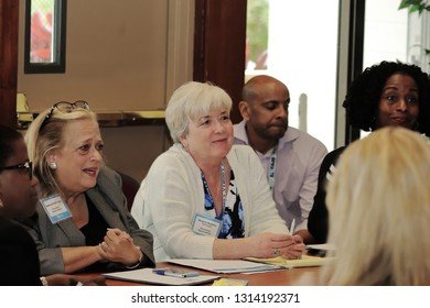 Davie, Florida / USA - January 30 2019: Broward County Census 2020 Kickoff meeting at Tree Tops Park older lady with grey and white hair wearing a white sweater and colorful blouse talking to a group