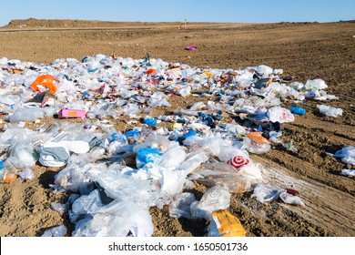 Davis, CA - February 19, 2020: An assortment of mixed garbage is strewn about the ground at a landfill.